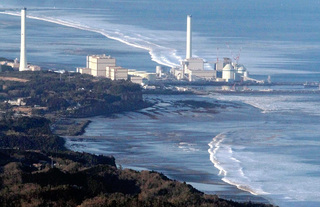 Hirono Power Station is seen as a wave approaches after an earthquake in Hirono Town, Fukushima Prefecture, March 11, 2011. (REUTERS/YOMIURI)